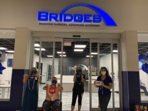 BRIDGES employees holding up communicator masks donated by the MWP