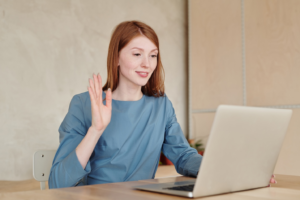woman holding up her hand in front of a laptop