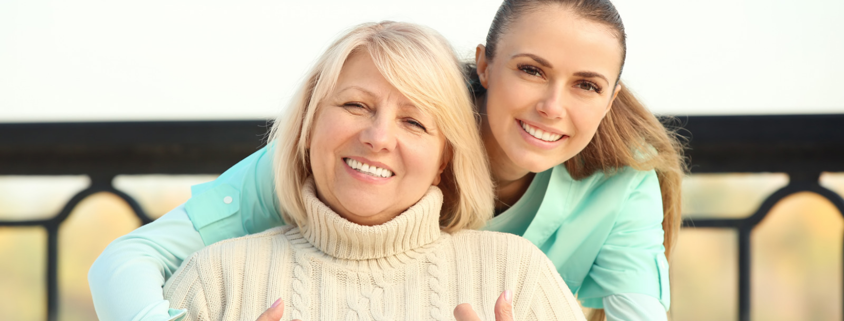 an elderly woan and young woman smiling together