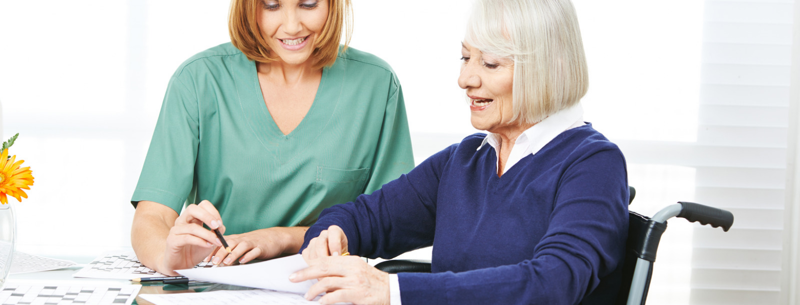 caregiver helping eldrly woman fill out forms