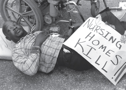 man chained to his wheel chair laying on the ground with a sign that says Nursing Homes Kill.