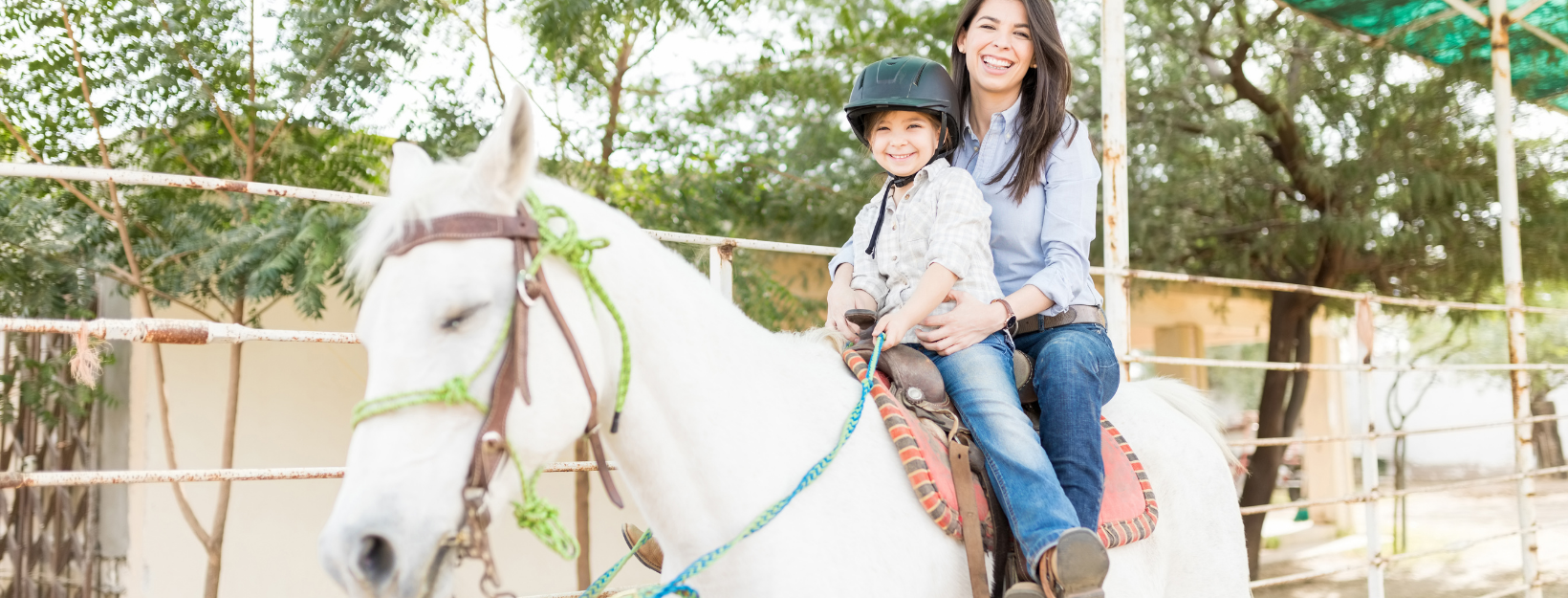 mother nd child smiling on a horse