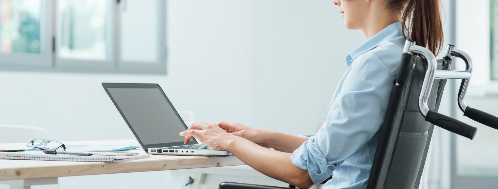 woman in manual char working in front of laptop