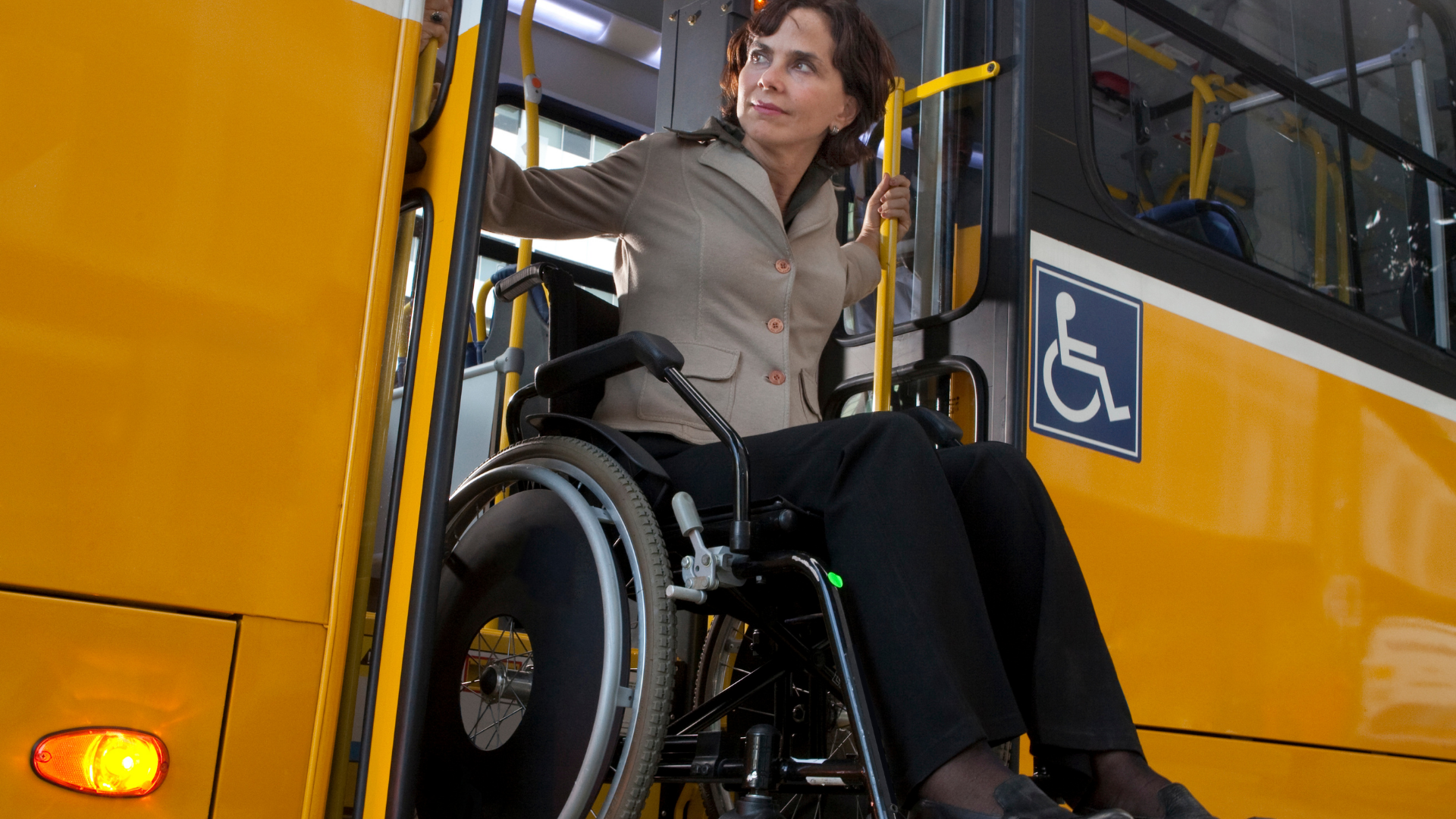 woman in manual wheelchair on bus lift