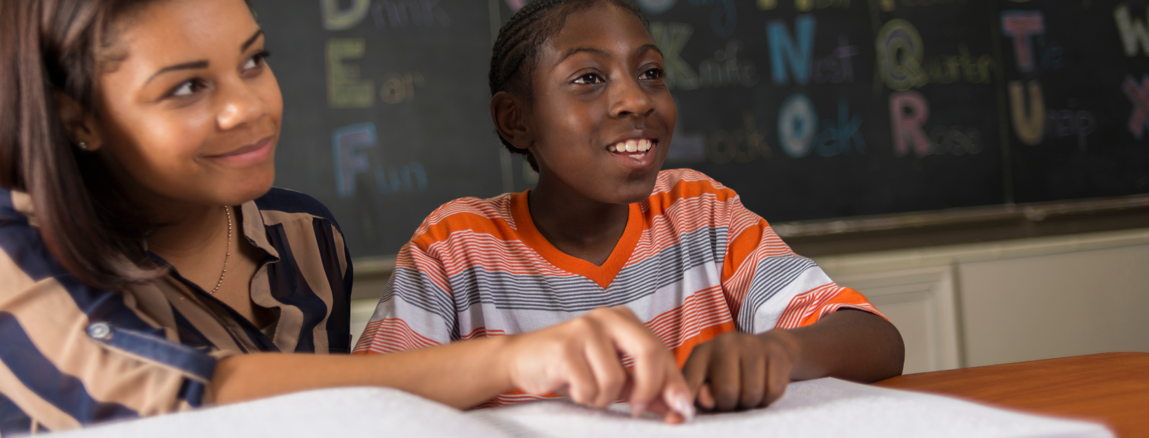 In a classroom, a young blind black male student wearing orange striped shirt who is learning to read Braille from his female teacher who is wearing a blue blouse with brown stripes