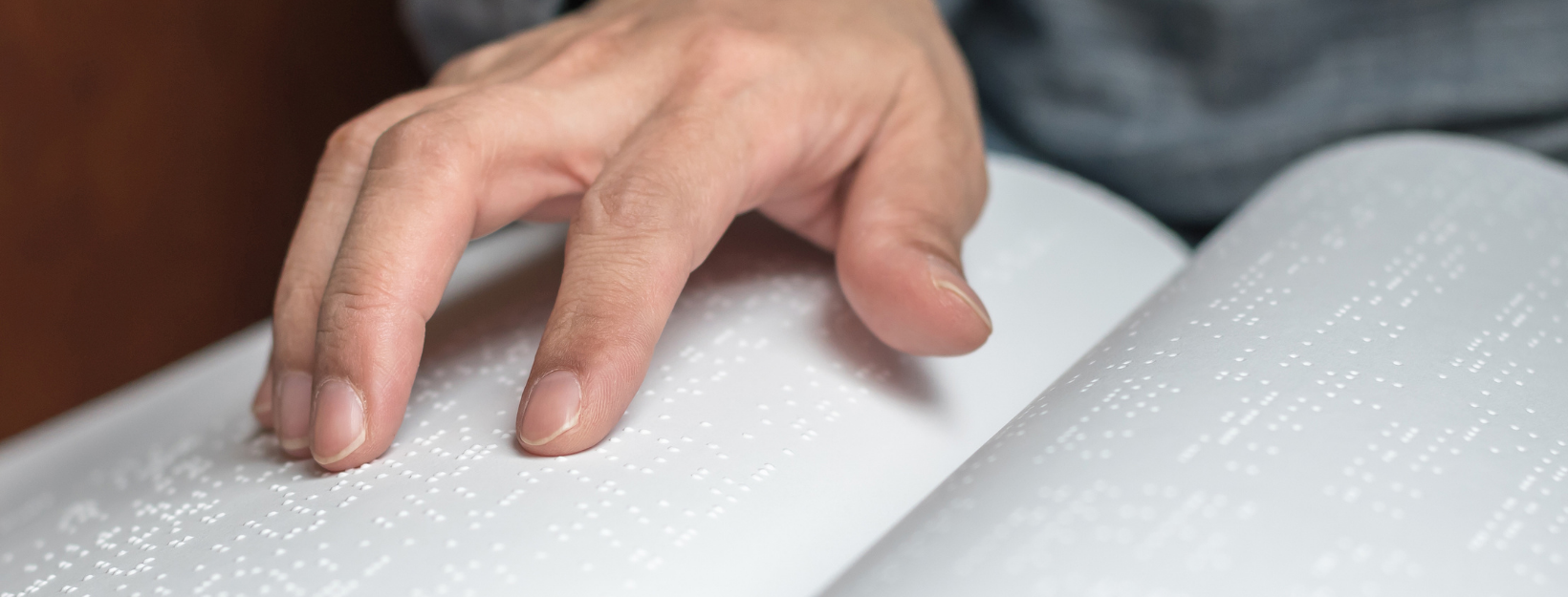 close up of a white man's fingers reading book in Braille